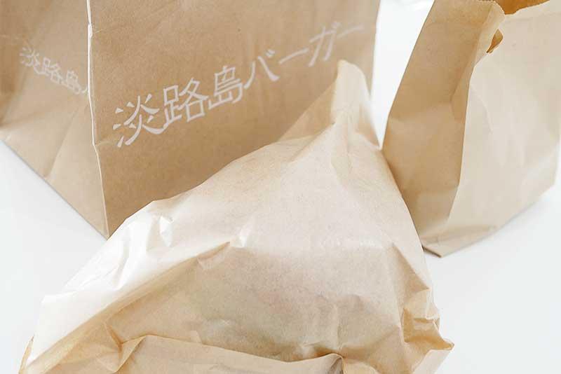 包み紙に入ったバーガーとポテト