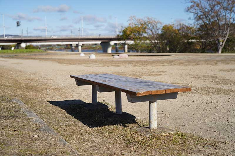 河川敷の公園にある木製のベンチ