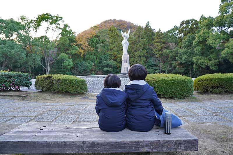 愛の像を見ながら座る兄弟