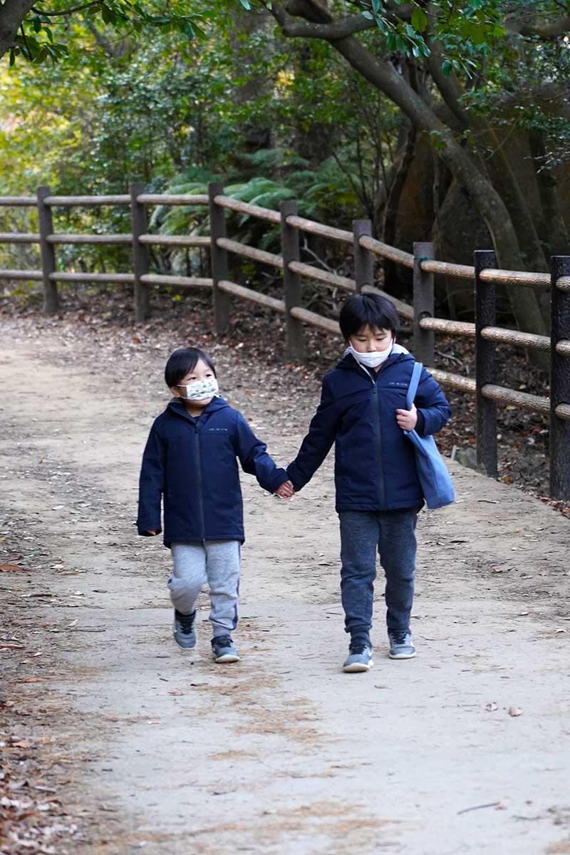 手を繋いで歩く兄弟