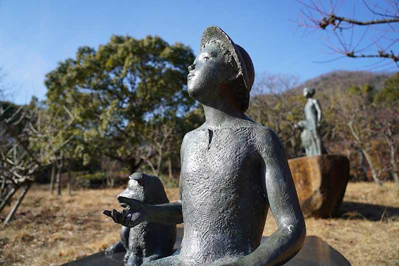 空を見上げる少年とイヌの銅像
