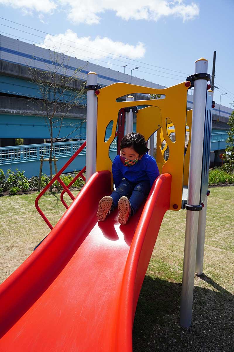 幼児用ゾーンの滑り台で遊ぶ6歳児