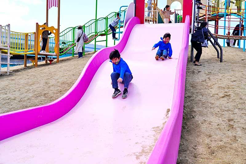 ピングの滑り台で遊ぶ小学生